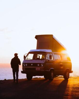 A man standing beside a VW westfalia pop top at dawn
