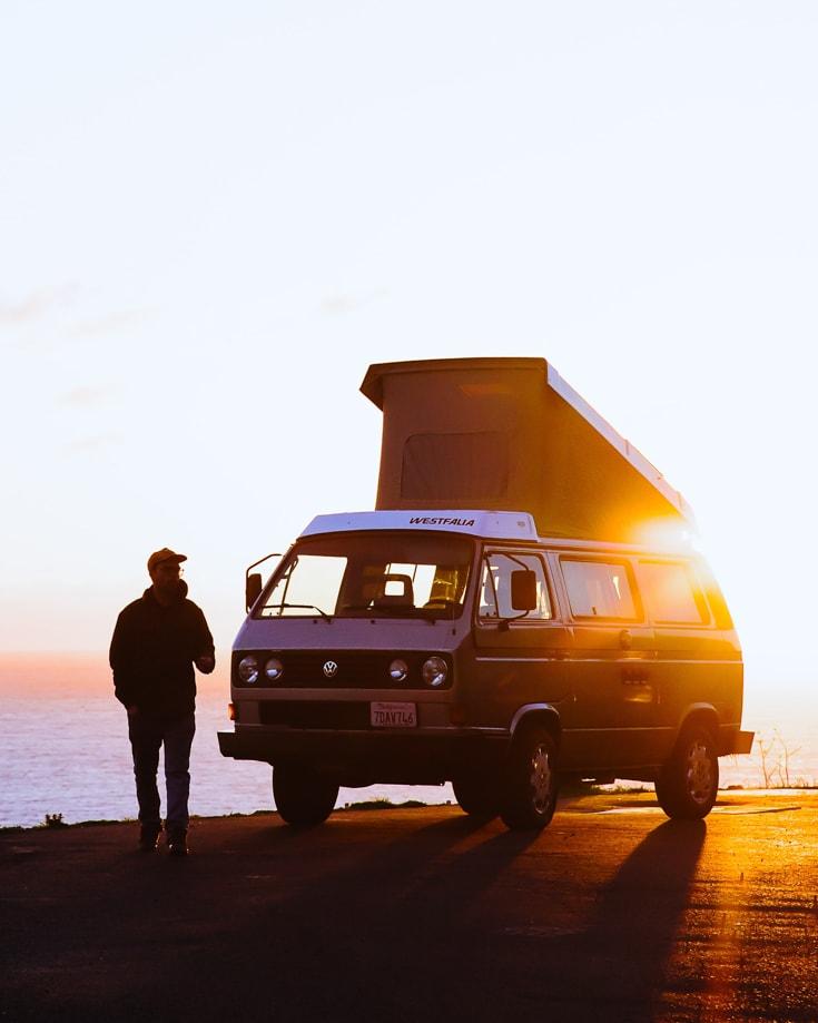 A man standing beside a VW kombi pop top campervan at sunset
