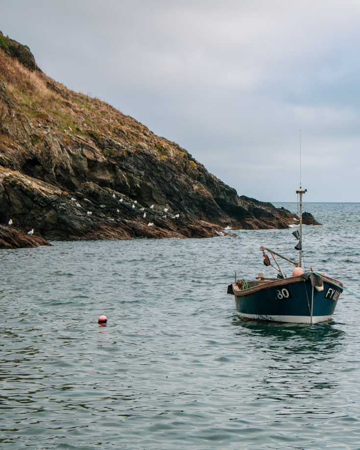 Small fishing boat moored at high tide in Portloe cove