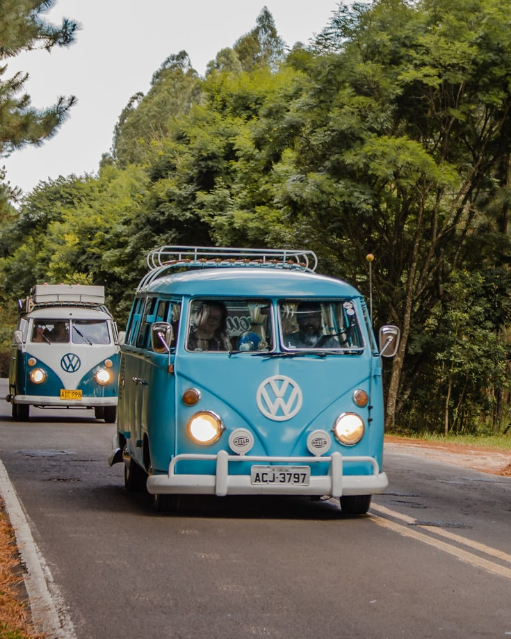 2 retro VW campervans driving in convoy along a road