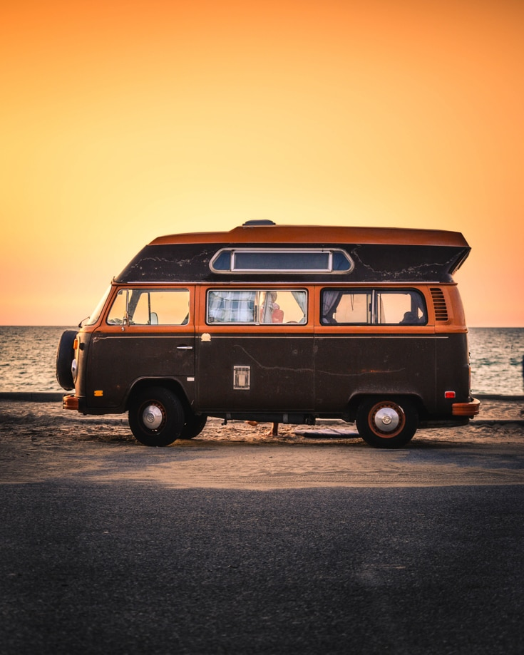 A campervan parked on the coast at sunset
