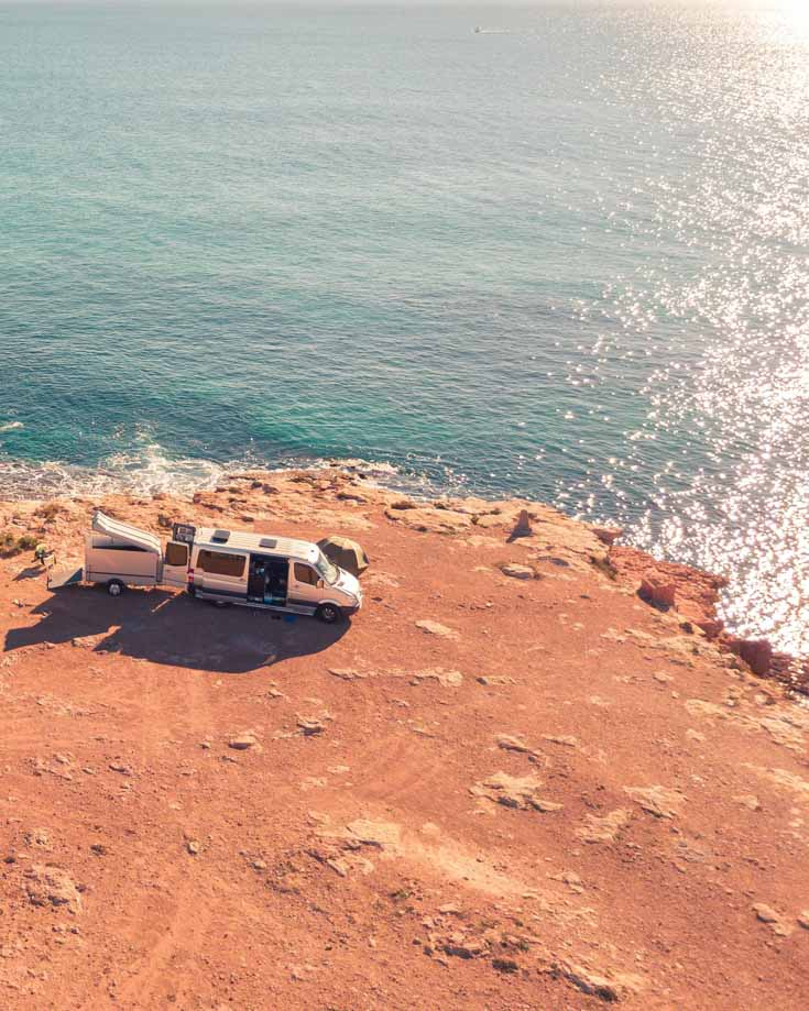 A camper with solar panels parked on a cliff edge