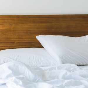 White cotton sheets and pillows on an unmade bead with a wooden headboard
