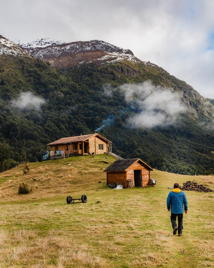 A man walking through the mountains towards a wooden cabin