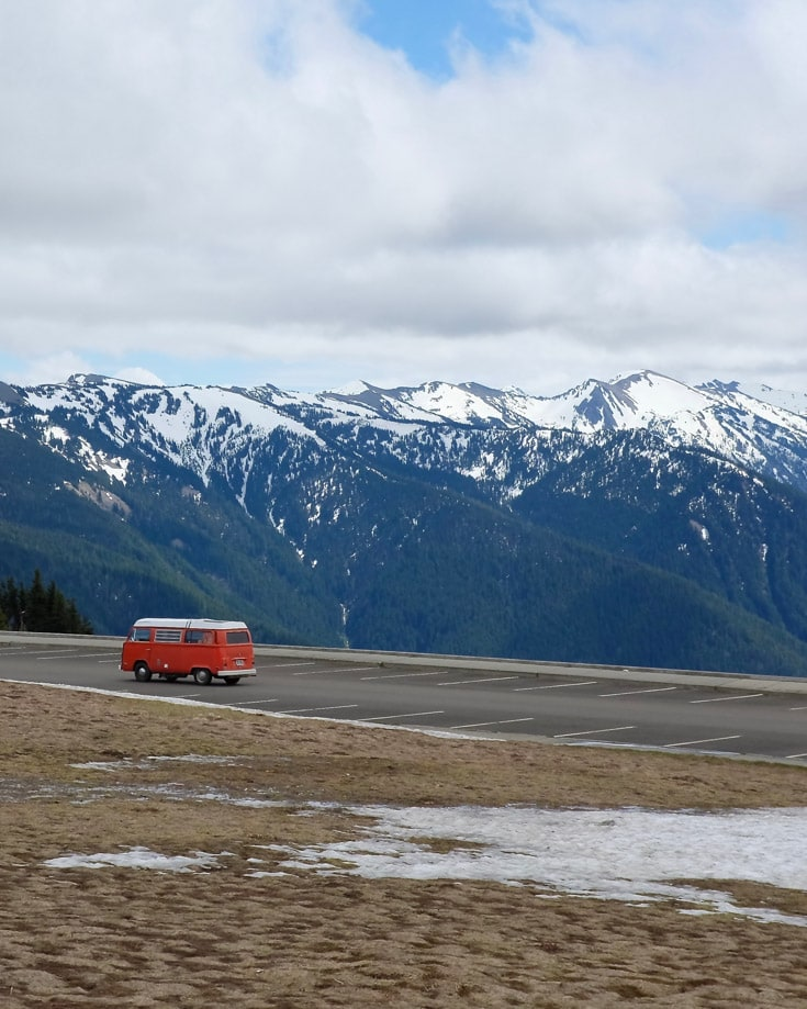 red campervandriving through a wintery mountain scene