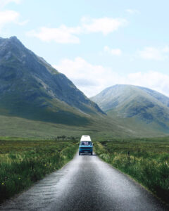a campervan drivin on a narrow lane surrounded by mountains