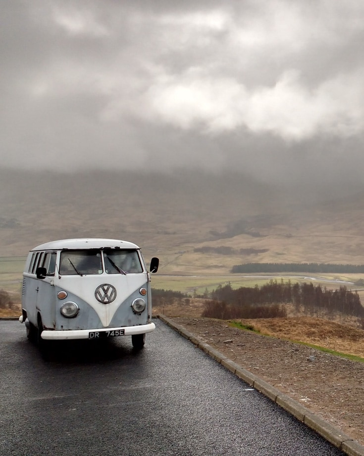 a retro VW camper parked up on a cloudy day overlooking a drab countryside scene