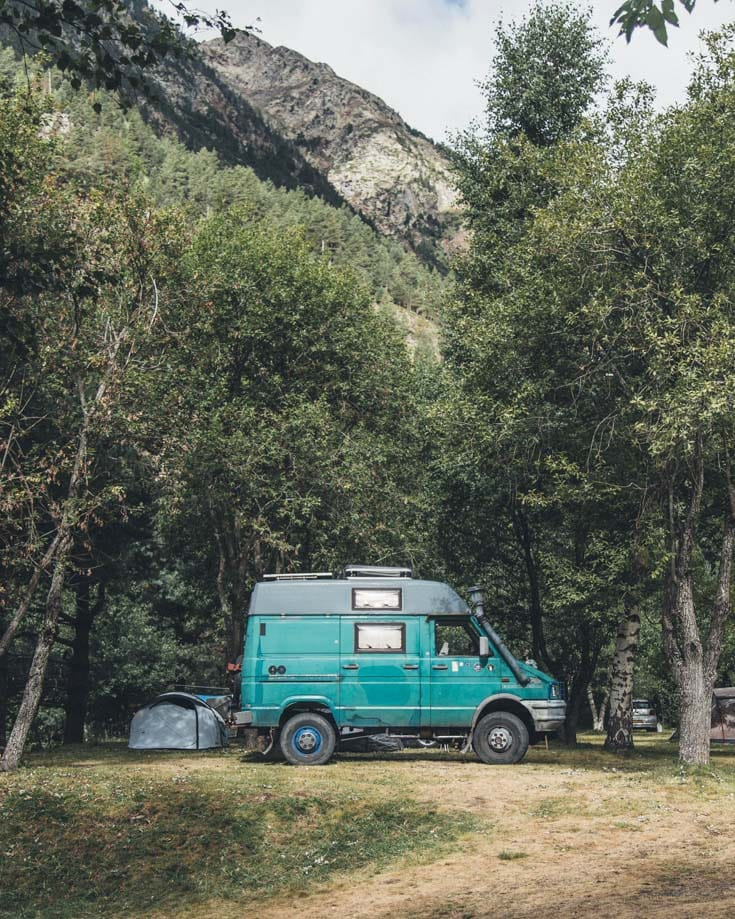 a campervan parked beneath trees