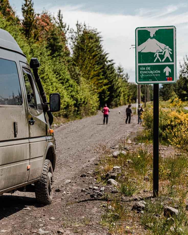 Mercedes Sprinter 4x4 camper van driving beside a Volcano warning sign