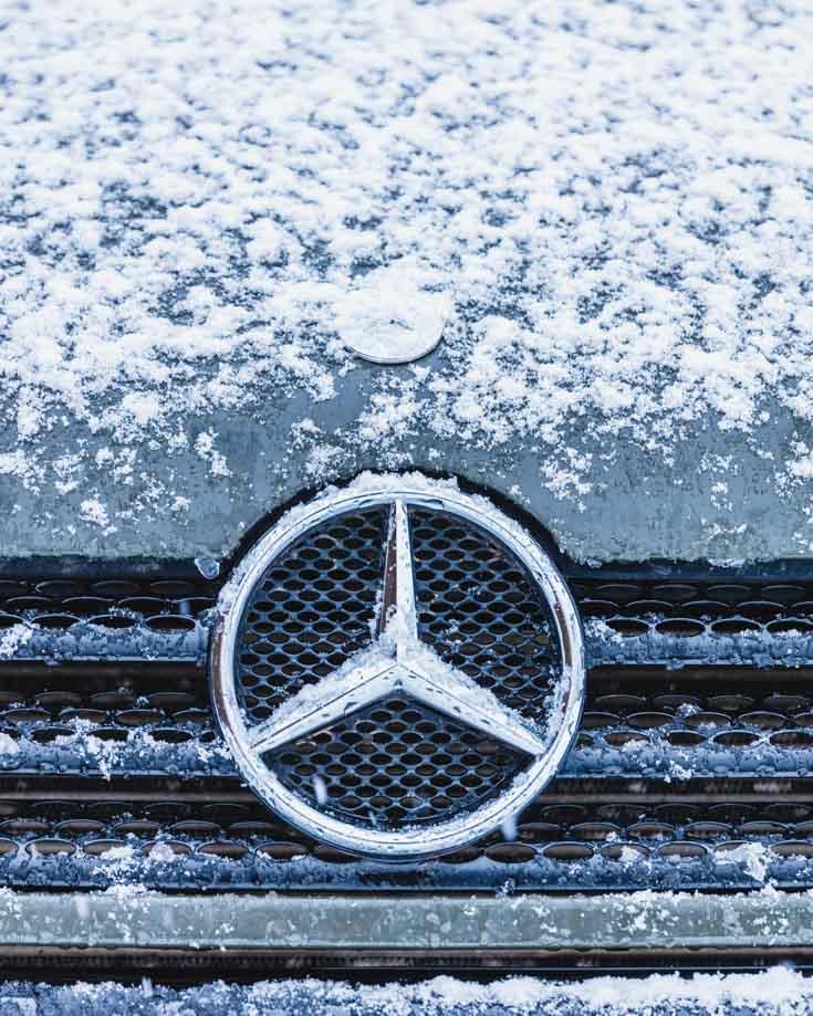 Close up of Mercedes Sprinter campervan badge snow covered