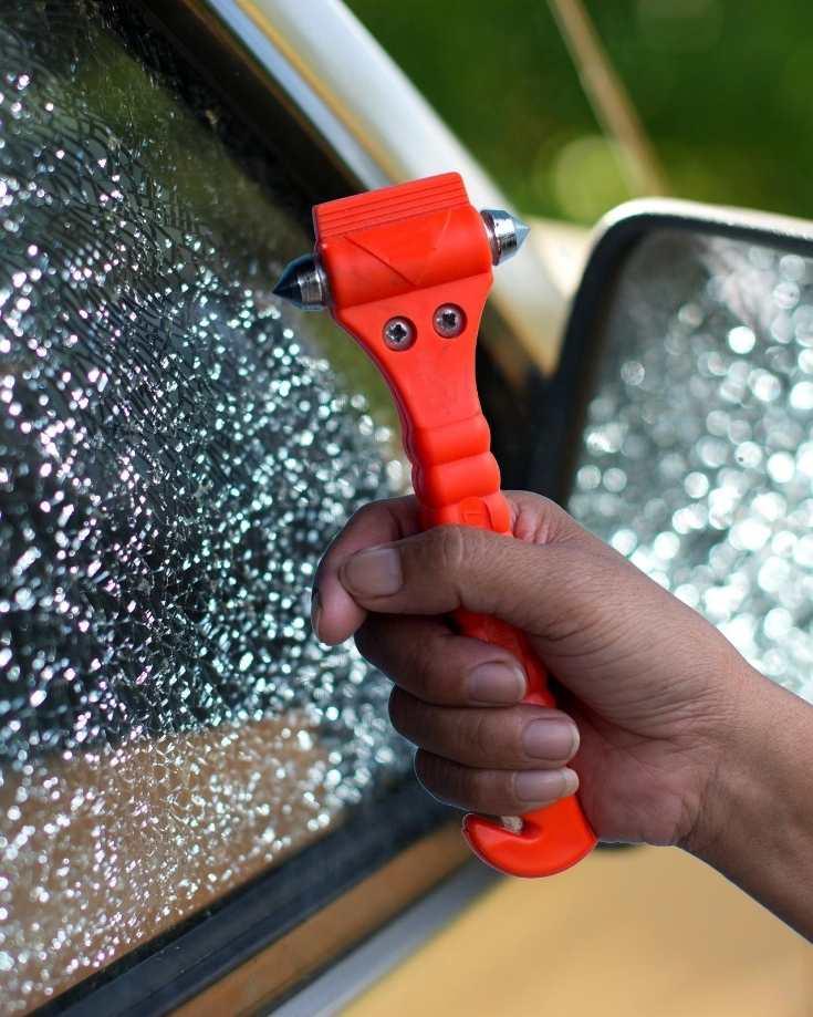 Using an emergency hammer to break a car window