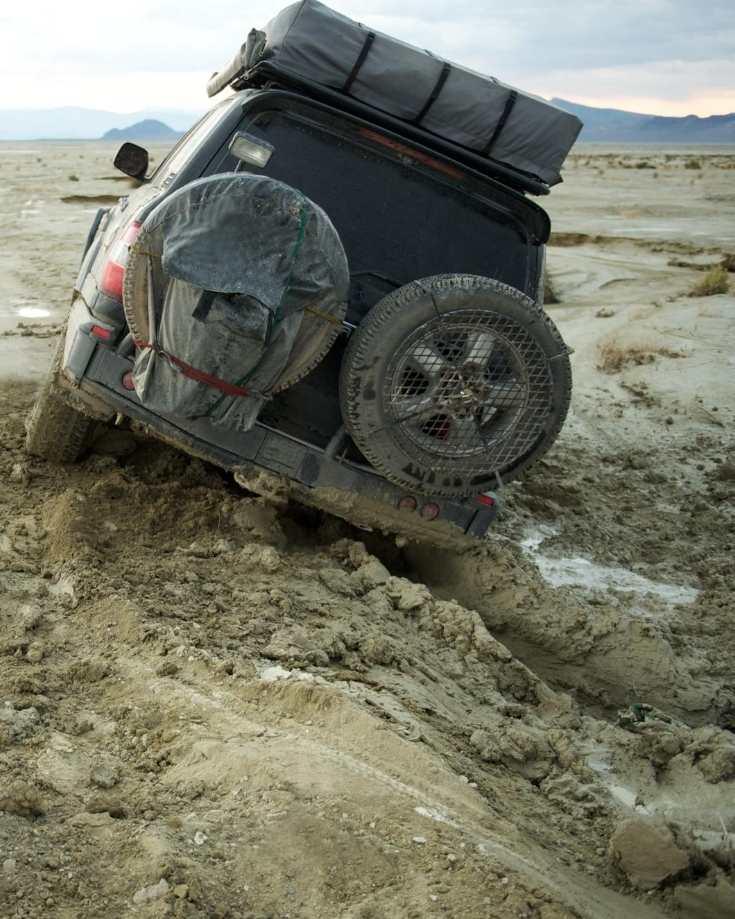 A 4x4 vehicle stuck in muddy ground
