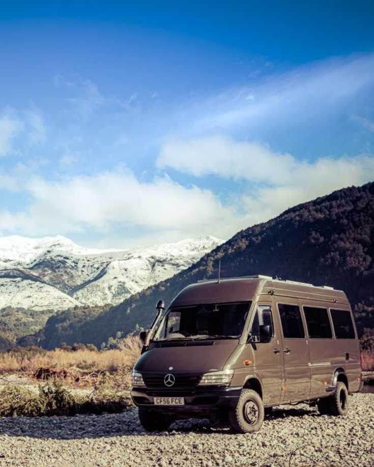 A Sprinter van conversion parked by a river in winter