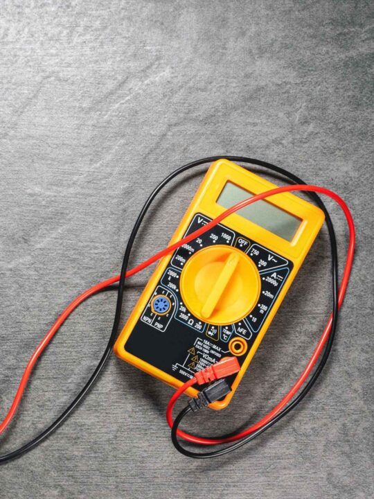 A brightly coloured multimeter with probes