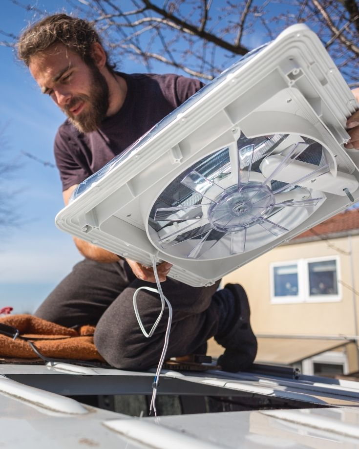 A man installing an RV roof vent on a campervan conversion Campervan Conversion