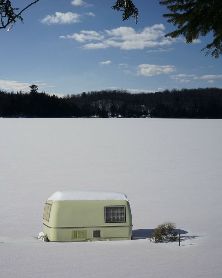 travel trailer camping in the winter, surrounded by deep snow