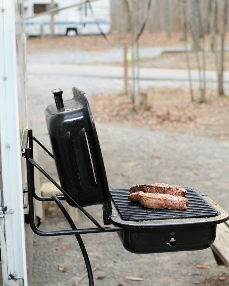 a portable grill mounted on the side of an RV