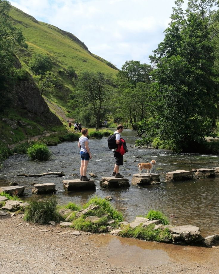 Hikers and their dog crossing the Stepping Stone over the River Dove