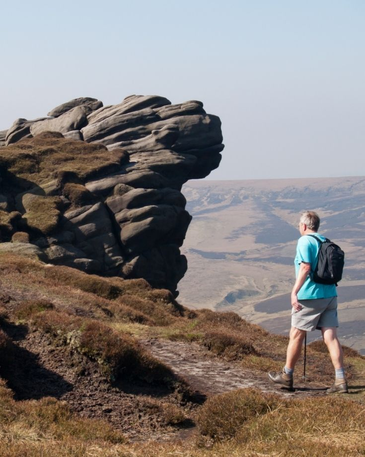 Hiker reaching the summit of Kinder Scout